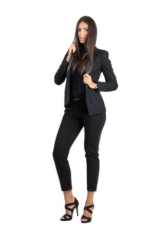 Young beauty in black formal suit posing while holding collar. Full body length portrait isolated over white studio background.