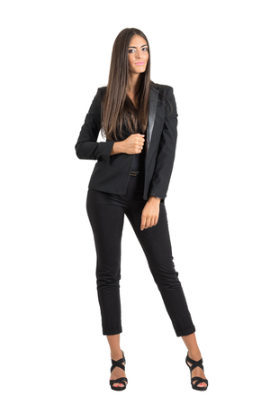 black pants: Pretty young tanned business woman posing and smiling while looking at camera.  Full body length portrait isolated over white studio background.