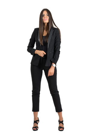 Gorgeous tanned business woman in formal wear confident posing at camera.  Full body length portrait isolated over white studio background. Stock Photo
