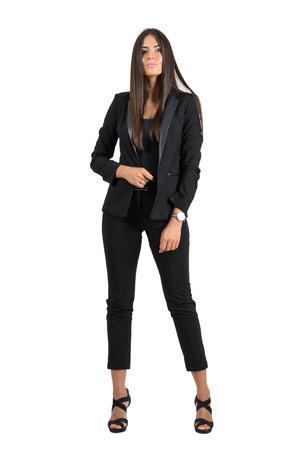 mujeres elegantes: Mujer de negocios bronceada magnífica en desgaste formal confía posando a la cámara. Cuerpo completo retrato de cuerpo entero aisladas sobre fondo blanco de estudio.