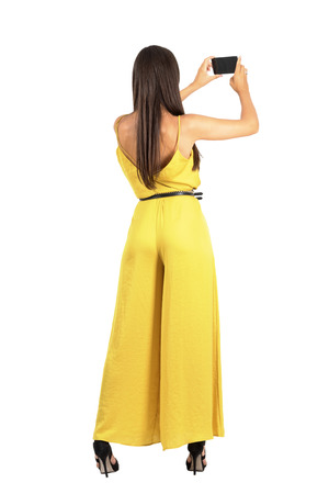 Rear view of young elegant woman taking photo with smartphone. Full body length portrait isolated over white studio background.