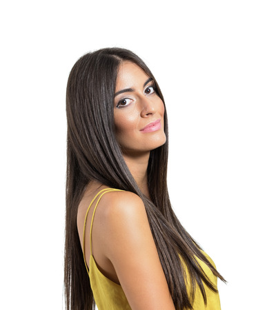 shy woman: Beautiful young smiling Latin woman with long straight healthy hair turning head to camera. Close up portrait isolated over white studio background.