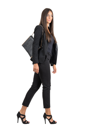 Elegant Latin business female in black suit and handbag walking side view.  Full body length portrait isolated over white studio background. Stockfoto
