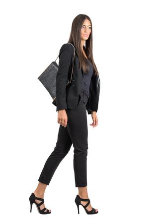 Elegant Latin business female in black suit and handbag walking side view.  Full body length portrait isolated over white studio background. Standard-Bild