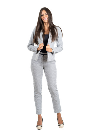 businesswoman suit: Sexy young business woman holding collar smiling at camera. Full body length portrait isolated over white studio background.