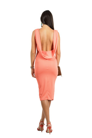 Rear view of sensual beauty in evening dress with bare naked open back walking away. Full body length portrait isolated over white studio background.