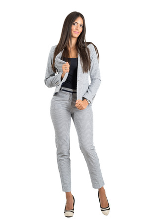 businesswoman suit: Confident business woman in formal stripped suit posing to camera. Full body length portrait isolated over white studio background.