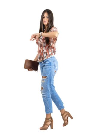 looking at watch: Side view of casual woman walking and checking time on hand watch. Full body length portrait isolated over white studio background. Stock Photo