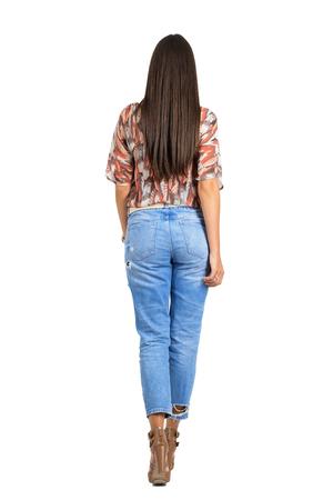 Achter mening van vrouw met lang haar in vrijetijdskleding weglopen. Full body lengte portret geïsoleerd op een witte achtergrond studio.