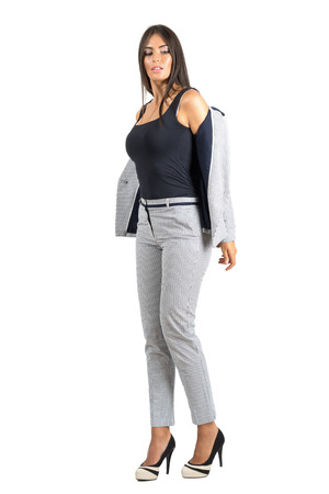 formal dressing: Sexy young business woman in formal wear taking off jacket. Full body length portrait isolated over white studio background.