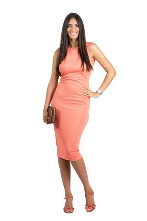body bag: Happy smiling beauty in elegant evening dress holding bag posing at camera.Full body length portrait isolated over white studio background. Stock Photo