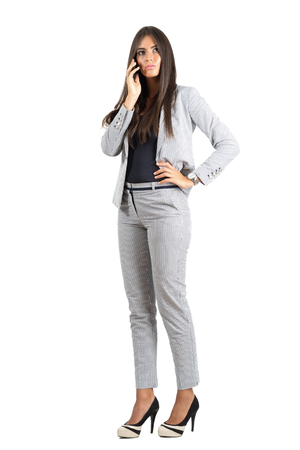 phone isolated: Serious corporate woman talking on the phone looking away.  Full body length portrait isolated over white studio background.