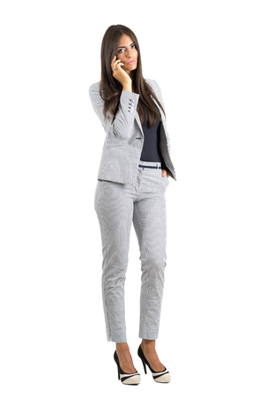 phone business: Serious worried corporate woman talking on the cellphone looking at camera.  Full body length portrait isolated over white studio background. Stock Photo