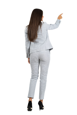in the back: Rear view of young business woman in suit pointing to the right.  Full body length portrait isolated over white studio background.