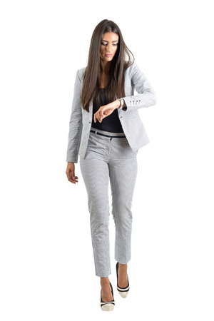 hurry up: Young businesswoman checking hand watch walking forward in the rush. Full body length portrait isolated over white studio background.
