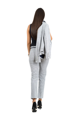 Rear view of business woman in formal wear holding jacket walking away.  Full body length portrait isolated over white studio background.