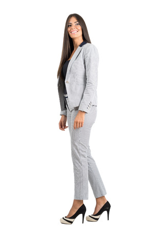 over white: Side view of smiling young business woman walking looking at camera. Full body length portrait isolated over white studio background.