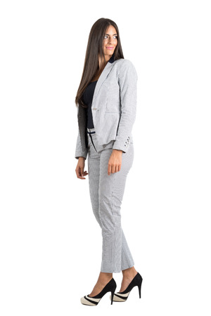 turn over: Side view of young businesswoman looking behind over the shoulder.  Full body length portrait isolated over white studio background.