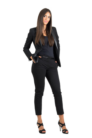 Confident bossy business woman in black suit with hands in pockets looking at camera.  Full body length portrait isolated over white studio background. Standard-Bild