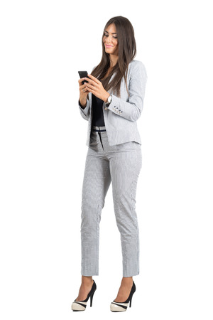 Young smiling formal dressed up woman texting with mobile phone.  Full body length portrait isolated over white studio background. Stockfoto