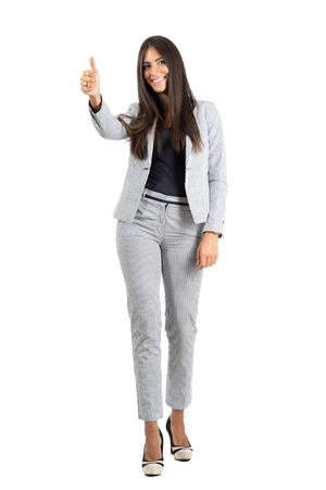 Cheerful smiling young business woman with thumbs up gesture.  Full body length portrait isolated over white studio background. Stockfoto