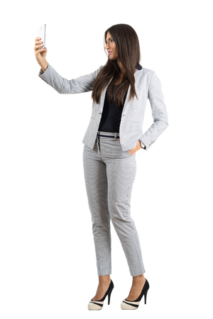 Profile view of young businesswoman taking selfie with cellphone.  Full body length portrait isolated over white studio background.
