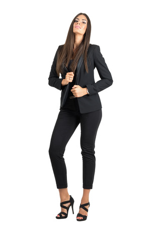 head collar: Seductive elegant beauty in black suit holding collar with head leaned back.  Full body length portrait isolated over white studio background.