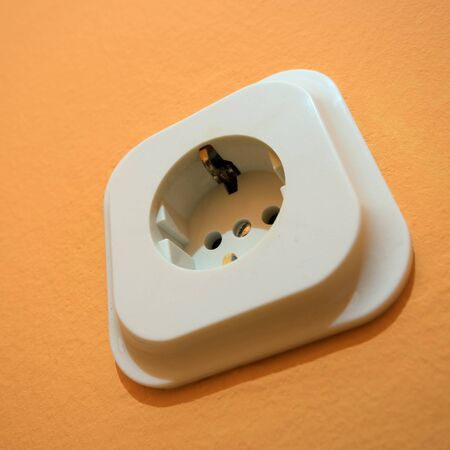 splitter: Close up macro of European electricity power outlet plug on the orange wall.