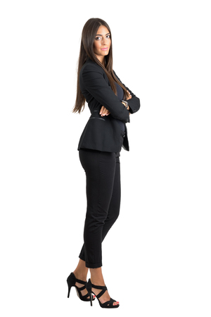 Side view of young successful business woman with crossed hands looking at camera.  Full body length portrait isolated over white studio background. Stockfoto