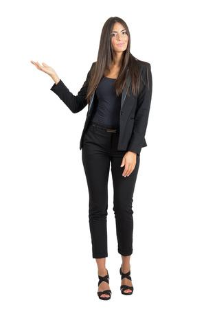 Attraktive Business-Mode Schönheit in der Klage mit den Händen auf Exemplar präsentiert. Ganzkörper-Länge Portrait über weißem Hintergrund Studio isoliert.