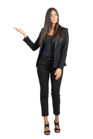 Attractive business fashion beauty in suit presenting with hands on copyspace. Full body length portrait isolated over white studio background. Foto de archivo