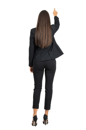 woman back view: Rear view of business woman in elegant suit pointing something in front of her. Full body length portrait isolated over white studio background.