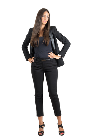 hands on hips: Serious elegant business woman in akimbo pose with hands on her hips.  Full body length portrait isolated over white studio background.