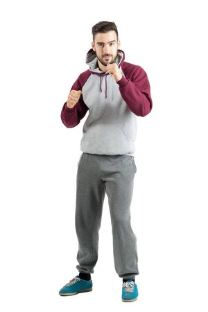 Young sporty casual man in sportswear with boxing hand gesture. Full body length portrait isolated over white studio background.