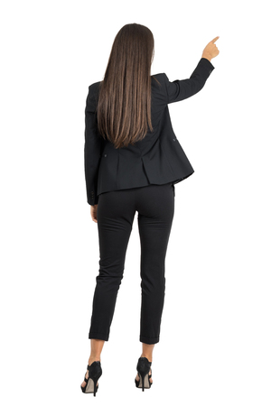 back screen: Rear view of long dark hair beauty pointing or presenting on her right side. Full body length portrait isolated over white studio background. Stock Photo