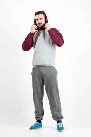 Young casual man in sportswear holding hoodie. Full body length portrait over gray studio background.