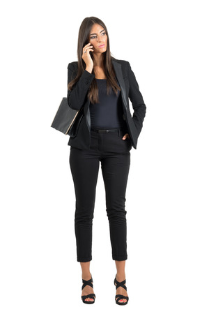 Serious worried business woman in suit talking on the mobile phone looking down. Full body length portrait isolated over white studio background. Foto de archivo