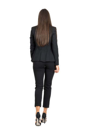 Elegant woman in business black suit walking away. Rear view. Full body length portrait isolated over white studio background.