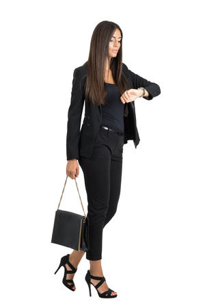 Attractive tanned business woman checking time while walking. Side view. Full body length portrait isolated over white studio background.