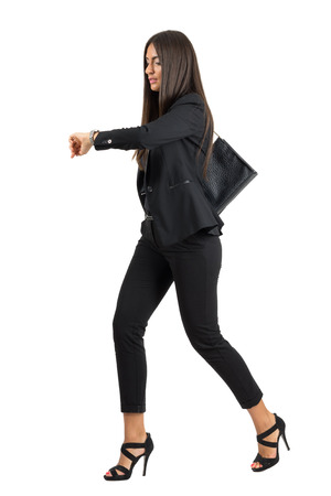 Young attractive businesswoman in suit running while checking time on her watch.  Full body length portrait isolated over white studio background.