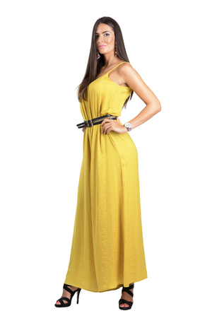 jumpsuit: Attractive sensual fashion woman in yellow jumpsuit posing with hand on hip. Full body length portrait isolated over white studio background.