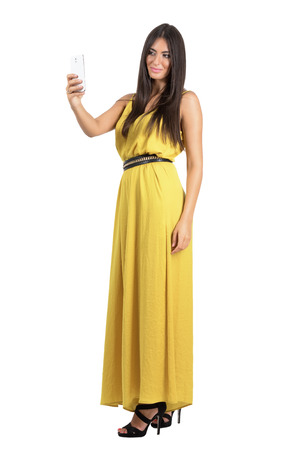 jumpsuit: Sensual gorgeous Hispanic woman in yellow jumpsuit taking cellphone selfie with one hand. Full body length portrait isolated over white studio background.