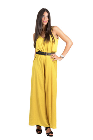 jumpsuit: Sexy Latino fashion model in yellow evening jumpsuit posing to camera. Full body length portrait isolated over white studio background.