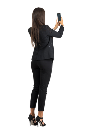 Rear view of long hair corporate woman in suit taking photo with mobile phone. Full body length portrait isolated over white studio background.