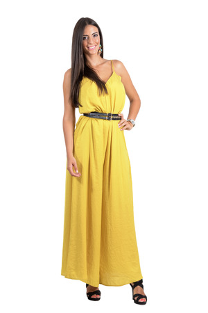 evening dress: Smiling posing fashion beauty in yellow jumpsuit with hand on her hip. Full body length portrait isolated over white studio background. Stock Photo