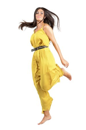 woman barefoot: Frozen motion of young beautiful woman in yellow jumpsuit jumping. Full body length portrait isolated over white studio background.