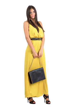 jumpsuit: Sensual attractive woman in yellow jumpsuit holding black leather bag. Full body length portrait isolated over white studio background. Stock Photo