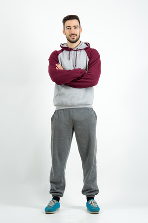 guy portrait: Young happy bearded casual man in sportswear with crossed hands. Full body length portrait over gray studio background.