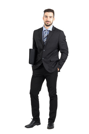 standing businessman: Friendly young confident business man holding documents folder smiling at camera. Full body length portrait isolated over white studio background.