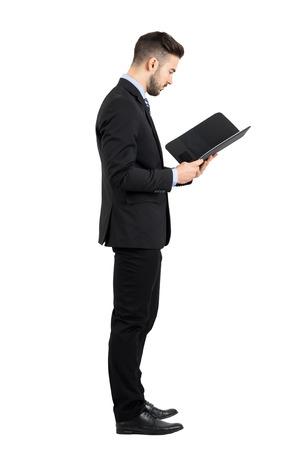profil: Biznesmen w garniturze czytania dokumentu lub widoku bocznym umowy. Pełna długość portret body izolowanych ponad białym tle studio. Zdjęcie Seryjne